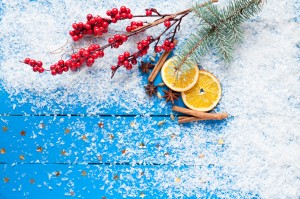 Christmas card. Spices, orange slices, Christmas tree and berries, stars, fake snow on the wooden background. Top view